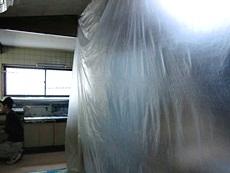 大山崎町のキッチンリフォーム。キッチン以外の物に工事で出るホコリがかからないようにビニールで保護します。