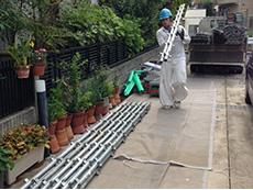 長岡京市の外壁塗装とバルコニーの増築リフォーム。工事の前に足場を立てます。足場の材料を運んでいるところです。