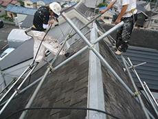 向日市の屋根塗装リフォーム。塗装前に高圧洗浄機を使って長年の汚れやほこりを洗い流しています。