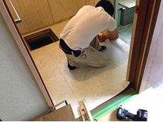 ライオンホームの洗面台リフォーム。床のタイルを張り替えているところです。洗面室の入口の段差を無くしました。