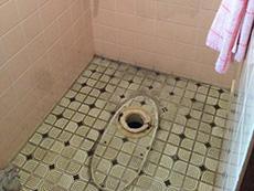 大山崎町のトイレリフォーム。便器を取り外したところです。取り外した床のタイルに長年の汚れが残っていました。洗剤でキレイに掃除をします。