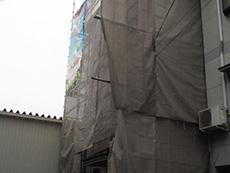 西京区の外壁塗装リフォーム。足場を組み立てた後、洗浄水や塗料が飛びちらないように、メッシュシートを張ります。
