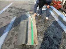 大山崎町の屋上防水リフォーム。古い防水シートの中に水が溜まっていたので、切り開いて水を抜きました。