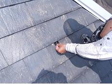 長岡京市の屋根外壁塗装リフォーム。屋根にタスペーサーという縁切り材を手で差し込んでいるところです。塗料で屋根同士がくっつかないようにする為に、これを差し込みます。