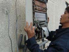 向日市で給湯器を交換しました。古い給湯器の前のパネルを開けて、電線の確認をしています。