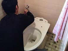 大山崎町のトイレリフォーム。新しい便器を取り付けています。リフォーム専用便器は大掛かりな配管工事が不要。2,3時間で美しいトイレに変身できます。