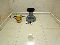 長岡京市のトイレリフォーム。排水の接続部材を床に取り付けました。