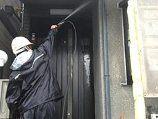 長岡京市の外壁屋根塗装リフォーム。玄関横の外壁を高圧洗浄機で洗っています。
