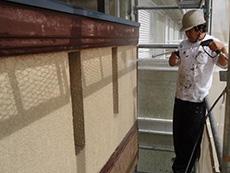 長岡京市の屋根外壁塗装リフォーム。外壁の汚れを高圧洗浄機で洗い流しています。