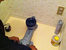 長岡京市のトイレリフォーム。新しい便器を取り付ける為の、リフォーム専用の排水アジャスターを取り付けます。