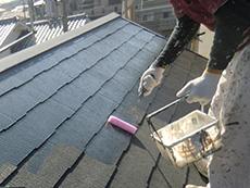 長岡京市の屋根外壁塗装リフォーム。屋根塗装の1回目は接着剤のような下塗り材を塗ります。乾くと透明になる塗料を手塗りローラーで塗っているところです。