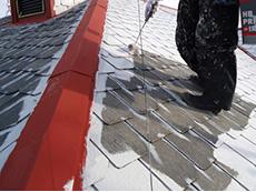 長岡京市の屋根外壁塗装リフォーム。屋根に塗料の密着を良くする下塗り材を塗っています。ライオンホームの塗装は手塗りローラーの3回塗りです。