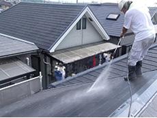 長岡京市の屋根外壁塗装リフォーム。屋根の汚れやコケを、高圧洗浄機で洗い流しています。塗料の密着を高める為の作業です。