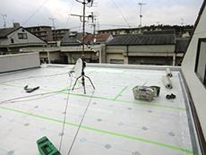 大山崎町の屋上防水リフォーム。緩衝シートの上から丸いグレーの平べったいお皿のようなディスクをたくさん取り付けます。このディスクで緩衝シートを押さえる役目をします。