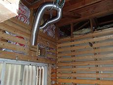 大山崎町の浴室・洗面室リフォーム。リフォーム施工中の浴室の壁に銀色の換気ダクトを付けるところです。昔の浴室には換気扇が無いので、新たにダクト配管をして換気扇を作ります。