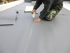 大山崎町の屋上防水リフォーム。塩ビシートを敷いたら、シートの継ぎ目を接着します。