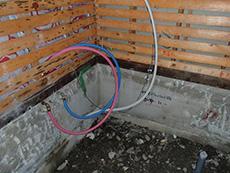 大山崎町の浴室・洗面室リフォーム。浴室の水・お湯・排水などのすべての配管の位置を変更します。ピンクとブルーの樹脂管で配管しています。