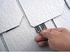 長岡京市の屋根外壁塗装リフォーム。黒いクリップのような物を、屋根材に手で差し込んでいます。カラーベスト同士が塗料でくっつかないように、カラーベスト全てに手で差し込みます。