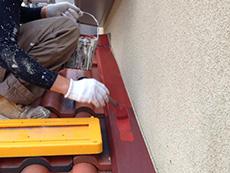 長岡京市の外壁塗装リフォーム。屋根の鉄板に錆止めを塗っています。
