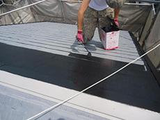 長岡京市の屋根外壁塗装リフォーム。2回目からは色の塗料を塗ります。ツヤのある黒色を塗っています。