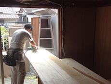 ライオンホームでリノベーション。作業中の大工さんです。平たい長い板を削っているように見えます。