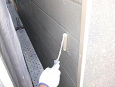 長岡京市の外壁屋根塗装リフォーム。接着剤のような下塗り材を手塗りローラーで塗っています。
