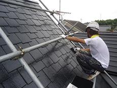 向日市の屋根塗装リフォーム。職人が足場を駆使して急勾配の屋根を塗っています。3回目の塗り重ねです。すでに光沢が素晴らしいですが、職人達からはツルツルしすぎて滑るので怖い!と言われるぐらいの塗料です。