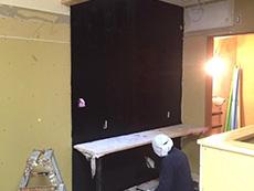 大山崎町のリビングリノベーション。キッチン横の壁を黒板にする為に専用の黒板塗料を塗っています。