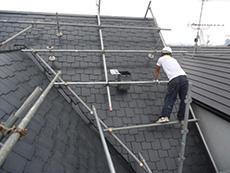 向日市の屋根塗装リフォーム。急勾配の屋根を、職人が丁寧に手塗りをしています。