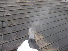 西京区の外壁塗装リフォーム。屋根を高圧洗浄機で洗い流しています。塗料の付着を高めるためには汚れやコケをしっかり落とします。