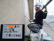 長岡京市の屋根外壁塗装リフォーム。外壁塗装の1回目、まず接着剤のような下塗り材を塗っています。