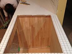 ライオンホームでリノベーション。オリジナル製作のキッチンの天板にタイルを張っているところです。真っ白の小さい四角いタイルを張っています。