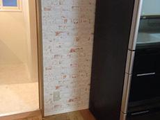大山崎町のリビングリノベーション。キッチンの 背中側の壁のクロスは白いレンガ調です。本物の煉瓦のように見えます。
