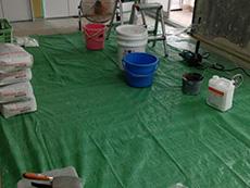 長岡京市の中古マンションリノベーション。漆喰を混ぜる準備が出来ました。床には緑のシートで汚れないように保護しています。