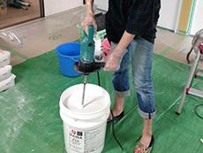 長岡京市の中古マンションリノベーション。入れ物に漆喰の粉と水、ウォールマイティという繊維のような物を入れて機械でかき混ぜています。機械を上下に動かして混ぜます。少し重いですが楽しい作業です。
