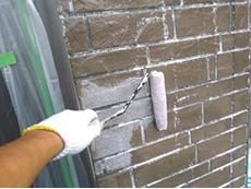 長岡京市の屋根外壁塗装リフォーム。外壁のサイディングに下塗り材を塗っています。乾くと白くなります。