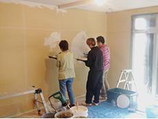 ライオンホームでリノベーション。お客様とライオンホームの田村と3人で、リビングの壁に漆喰を塗っているところです。田村が塗り方を教えています。