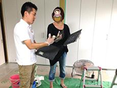長岡京市の中古マンションリノベーション。お客様とライオンホーム代表の田村です。漆喰を乗せる板を持って、漆喰を塗るコテの使い方をご指導しているところです。