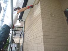長岡京市の屋根外壁塗装リフォーム。外壁を手塗りローラーで塗っています。