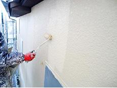 長岡京市の屋根外壁塗装リフォーム。外壁3回目を塗っています。アイボリーのような色です。全て手塗りで行います。