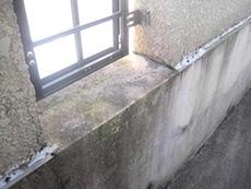 長岡京市の屋根外壁塗装リフォーム。リフォーム前のベランダの壁です。汚れとコケで緑色になり、雨水も弾かない状態です。