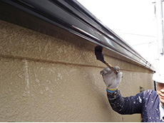 長岡京市の屋根外壁塗装リフォーム。雨樋に2液性シリコン樹脂の塗料を塗っていきます。屋根と同じスチールグレーの色で塗ります。