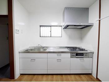 長岡京市のキッチンリフォーム。新しいキッチンは白色のリクシルのシエラ。壁は白いキッチンパネルになって掃除も楽になります。シンク下スライド引き出し収納は、足元のケコミ部分にまで収納スペースがあります。