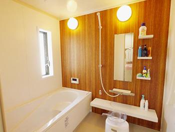お風呂浴室リフォーム。リフォーム後の浴室です。明るい茶色の木目調の壁パネルは高級感があります。お湯が冷めにくく、汚れがつきにくい リクシルのリノビオ。冬でも冷たさを感じにくい床は、キレイサーモフロアです。