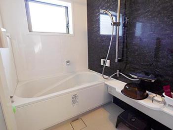 長岡京市のお風呂浴室リフォーム。リフォーム後の浴室です。リクシルシステムバス、リノビオ。カラーはストーンモザイクです。黒い石目調の壁パネルです。