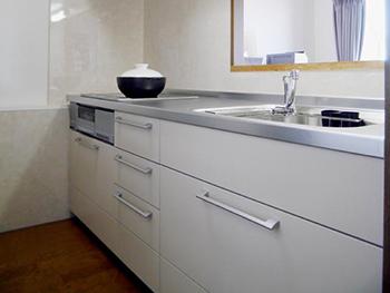 ライオンホームでキッチンリフォーム。リフォーム後のキッチンです。ベージュカラーのスライド引き出しタイプのキッチンです。キッチンの周りの壁はキッチンパネルを張りました。お掃除も楽です。