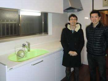 大山崎町のキッチンリフォーム。新しいキッチンの横で、笑顔のお客様と記念撮影の写真です。新しいキッチンの流し(シンク)はアップルグリーン、で他はホワイトです。