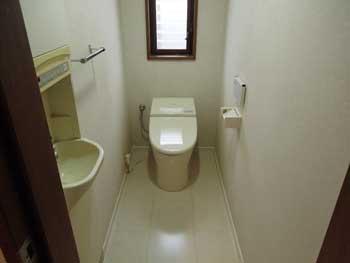 長岡京市のトイレリフォーム。リフォーム後のタンクレス便器トイレです。見た目もスッキリしてお掃除も楽になります。白いクロスと白い床で明るいトイレになりました。
