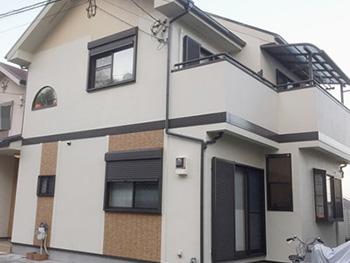 長岡京市の屋根外壁塗装リフォーム。塗装後の外観です。新築のように美しくなりました。全体的に白っぽい外壁に、こげ茶色と明るい茶色のアクセントが入っています。