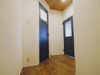 大山崎町の円団団地リノベーション。リフォーム後の玄関を入ったところです。白い壁に青いドアが2つ見えます。左の青いドアは寝室へ。右の青いドアはLDKへの入口です。